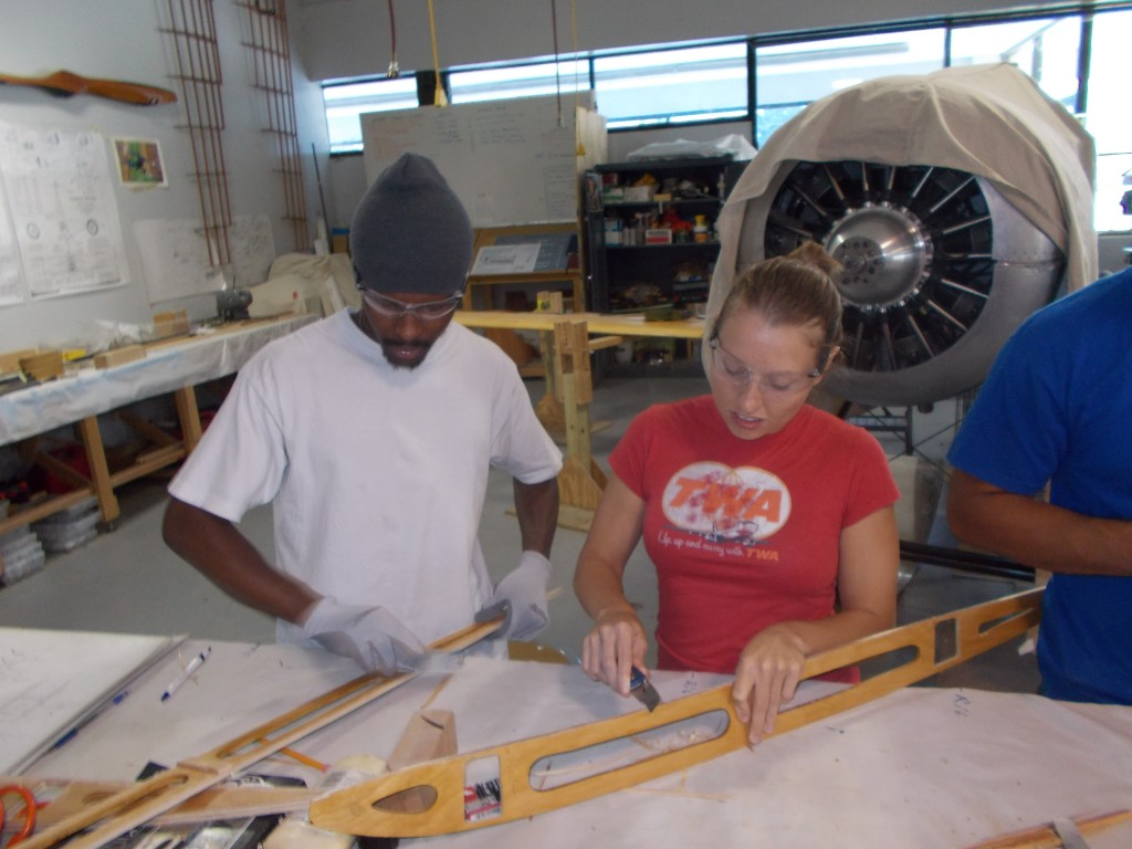 Darren Francis and Maria Liberto work on stripping the glue off the ribs at the aviation career school. We learned that without soaking the wood first, the capstrips were too springy to conform to the ribs curve.